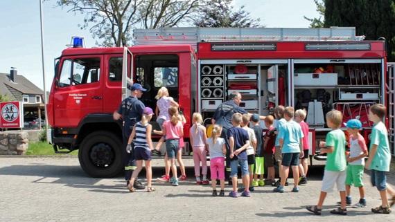 Feuerwehrhauptmann Frank Claren erklärt den Kindern des Ferienprogramms den TLF16 (Tanklöschfahrzeug)