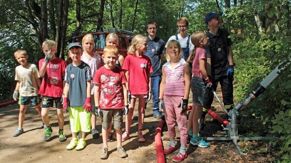 """Feuerwehrmann Broder Vollertsen erklärt den Kindern des Ferienprogramms einen Wasserwerfer und lässt sie """"den Waldbrand"""" löschen"""
